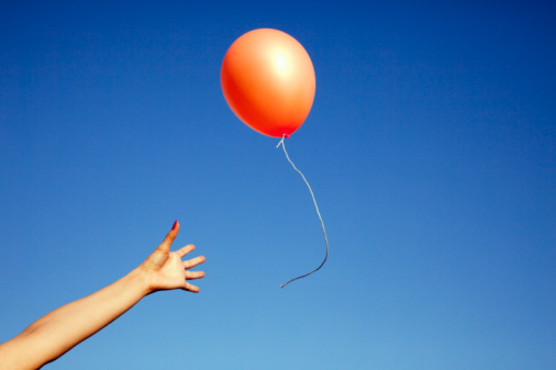 91538368-womans-arm-reaching-for-a-floating-balloon-gettyimages